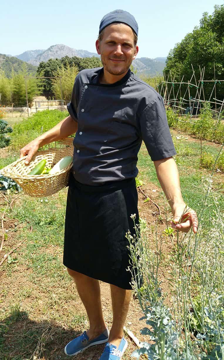 Marcelo mit seinem Körbchen unterm Arm im eigenen Bio-Garten