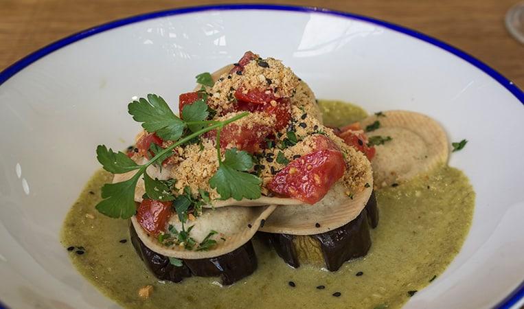 Raviolo gefüllt mit Spinat, Tofu, Pilzen und Cashewkernen auf gebackenen Auberginen mit einer Ricotta-Kräuter-Sauce