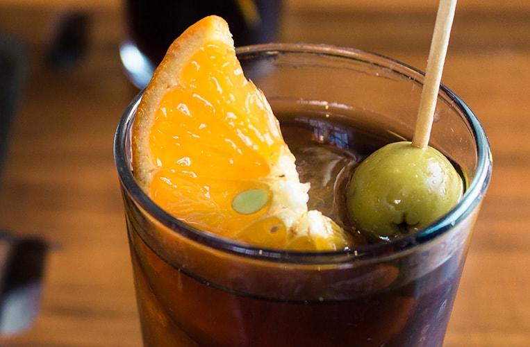 Vermuth mit Eis, einer Olive und einer Scheibe Orange