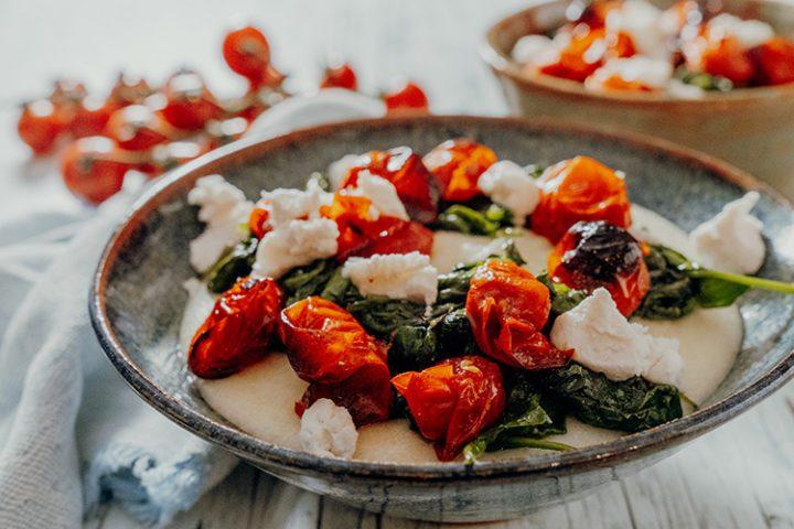 Cremige weiße Ziegenkäse-Polenta mit Tomaten und Spinat